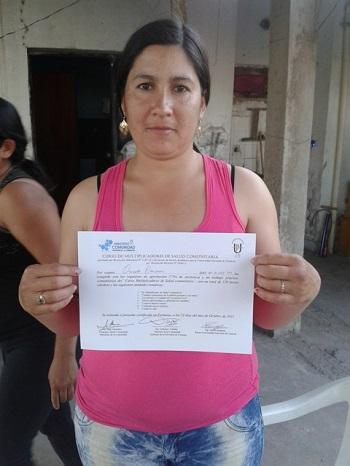 Vecina del barrio 20 de Julio con su certificado