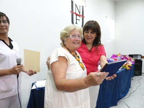 La decana Molina hace entrega de una plaqueta de reconocimiento